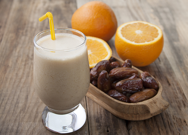 Smoothies of orange and dates with yogurt in a glass on a wooden table.